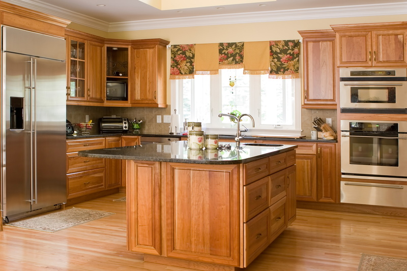 a pristine looking kitchen with wood flooring, island, and cabinets