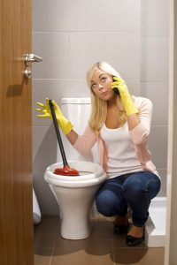 woman with plunger at her toilet, while on the phone