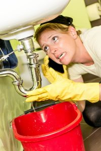 woman under sink looking at the pipe in panic