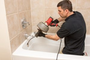 Plumber unclogging a tub drain with an electric auger.