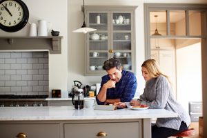 young-couple-looking-at-tablet-in-kitchen