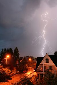 neighborhood-under-dark-sky-with-lightning