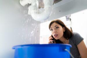 woman-on-phone-viewing-leak-under-sink